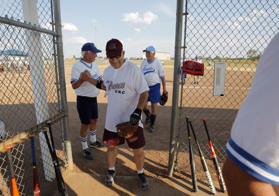 Photo -  SENIOR CITIZENS / SENIOR SOFTBALL: Jerry Dyre greats teammates on his way in to the dugout during a game at the Plex in Oklahoma City, July 19, 2011.  Dyre played for the Oklahoma City Royals because they were short one person.  Photo by Garett Fisbeck, The Oklahoman ORG XMIT: KOD