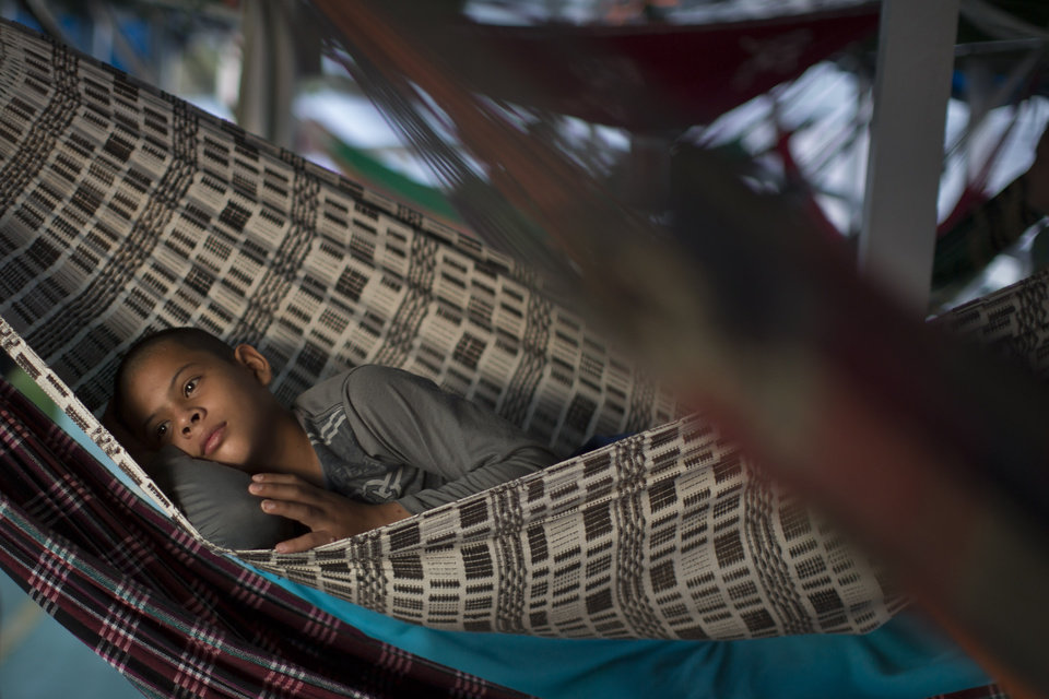 """Photo - In this May 22, 2014, photo, a boy rests on a hammock as he travels in the  """"Almirante Barbosa"""" regional boat, on the Solimoes river near Manaus, Brazil. Potential travelers would be wise to board ship well ahead of the scheduled departure and bring a hammock. Stalls in Manaus' Adolpho Lisboa market in front of the port, and a row of stores behind the market, have hammocks for every budget. (AP Photo/Felipe Dana)"""