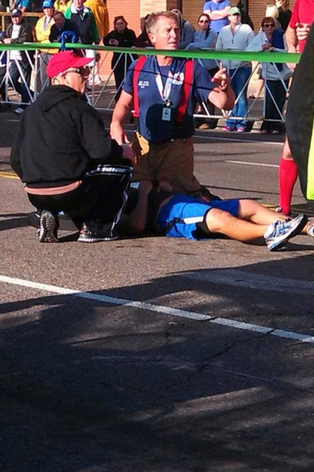 Irving, Texas fireman David Lewis helps a collapsed marathoner Sunday during the Memorial Marathon.   <strong></strong>