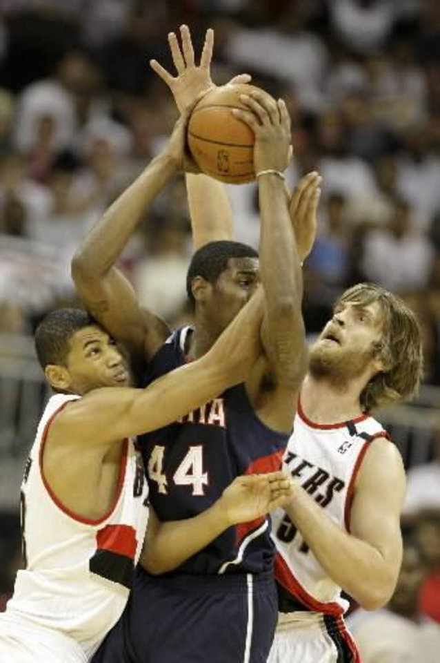 Portland Trail Blazers' Nicolas Batum, left, and  Steven  Hill, right, pressure Atlanta Hawks' Solomon Jones during the first quarter of their NBA preseason basketball game Friday, Oct 10, 2008 at the Sprint Center in Kansas City, Mo. AP Photo/Charlie Riedel