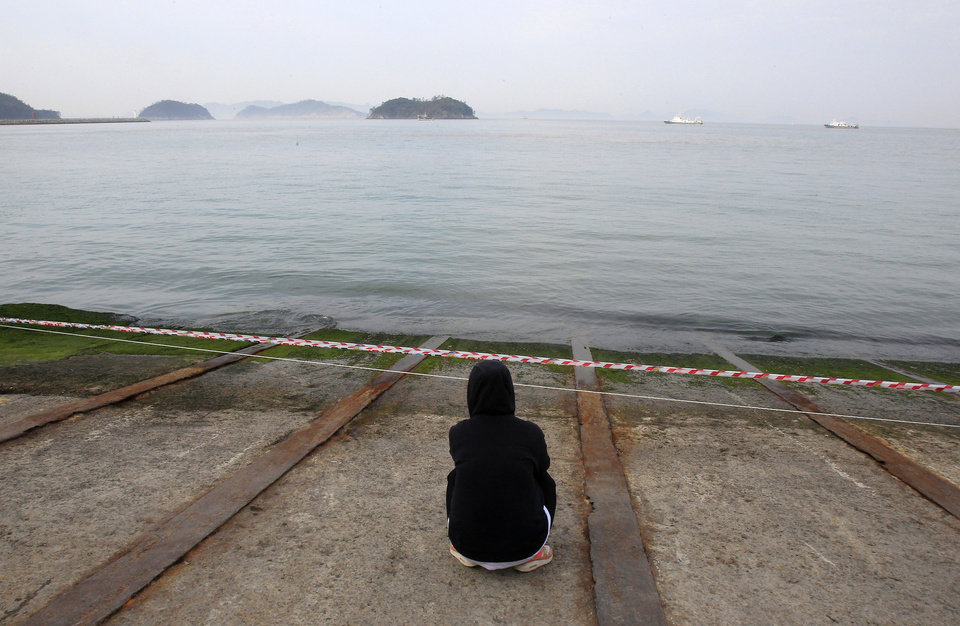 Photo - A relative of a passenger aboard the sunken Sewol ferry looks toward the sea as she awaits news on her missing loved one at a port in Jindo, South Korea, Tuesday, April 22, 2014.  As divers continue to search the interior of the sunken ferry, the number of confirmed deaths has risen, with about 220 other people still missing.  (AP Photo/Ahn Young-joon)
