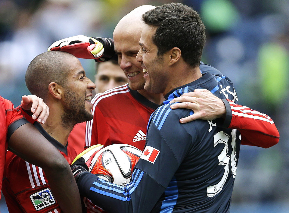 Photo - Toronto FC's Jermain Defoe, left, celebrates with goalkeeper Julio Cesar, right, and midfielder Michael Bradley, center, after they defeated the Seattle Sounders 2-1 in an MLS soccer match on Saturday, March 15, 2014, in Seattle. (AP Photo/Ted S. Warren)
