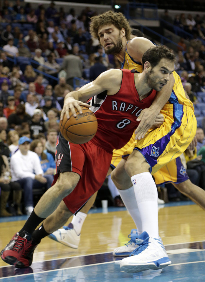 Toronto point guard Jose Calderon (8) drives around New Orleans center Robin Lopez (15)during the first quarter of an NBA basketball game at the New Orleans Arena in New Orleans, Friday, Dec. 28, 2012. (AP Photo/Dave Martin)