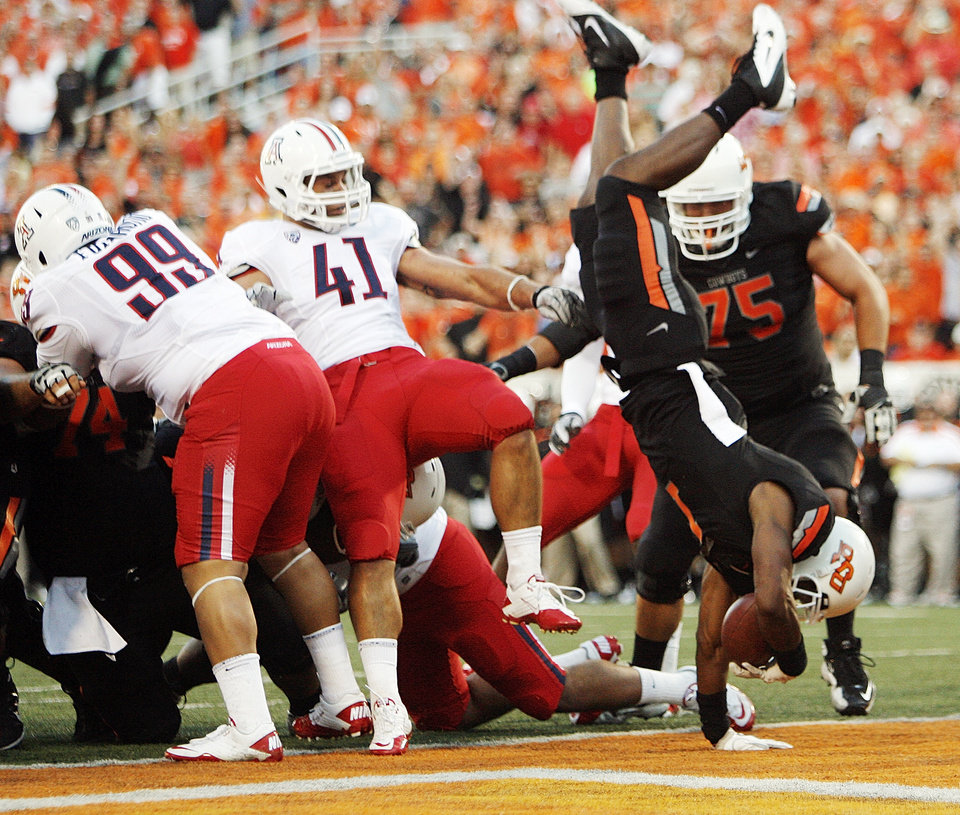 Oklahoma State's Joseph Randle (1) leaps into the end zone past Arizona's Saneilia Fuiamaono (99) and Paul Vassallo (41) in the first quarter Thursday. PHOTO BY NATE BILLINGS, The Oklahoman