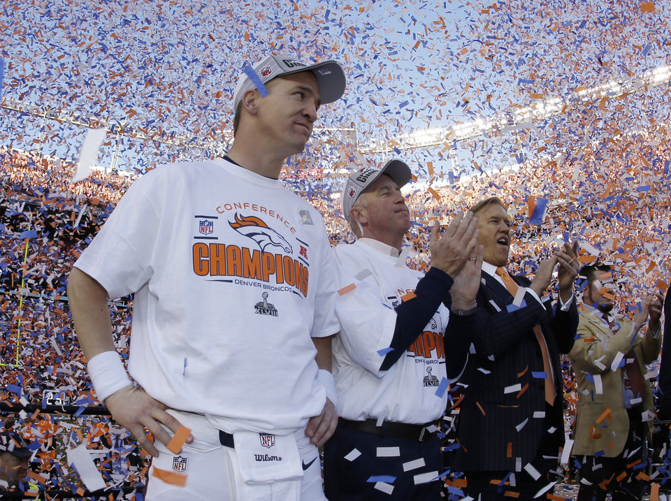 Photo - Denver Broncos quarterback Peyton Manning, stands with Broncos' head coach  John Fox and Broncos VP John Elway during the trophy ceremony after the AFC Championship NFL playoff football game in Denver, Sunday, Jan. 19, 2014. The Broncos defeated the Patriots 26-16 to advance to the Super Bowl. (AP Photo/Charlie Riedel)