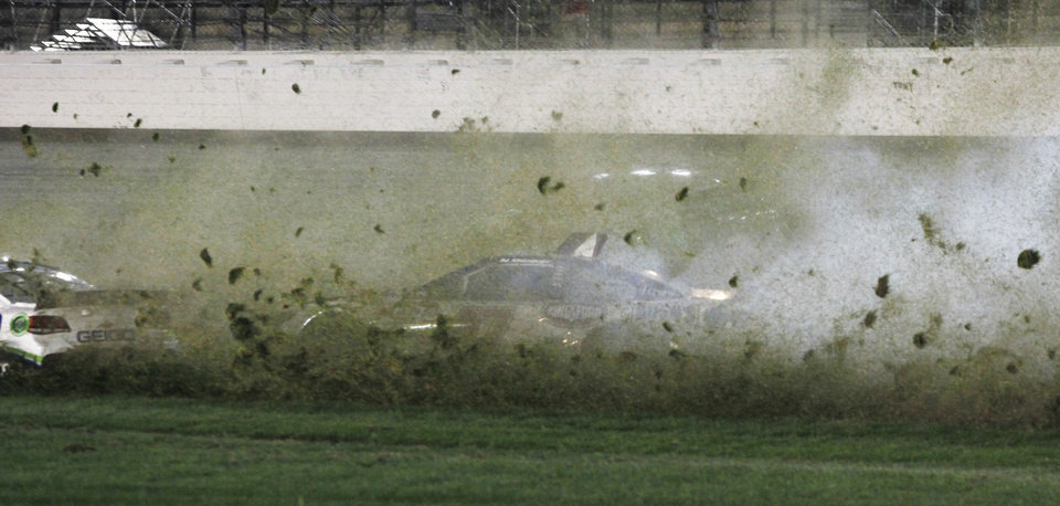 Photo - AJ Allmendinger (47) spins into the infield grass behind Casey Mears, left, during a NASCAR Sprint Cup Series auto race at Kansas Speedway in Kansas City, Kan., Saturday, May 10, 2014. (AP Photo/Colin E. Braley)