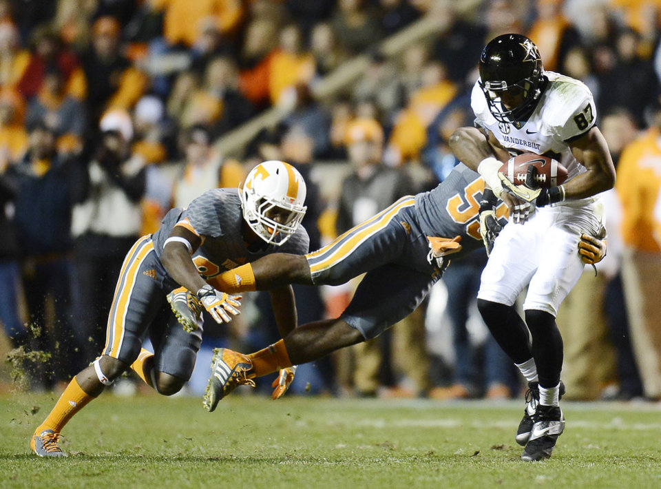 Vanderbilt wide receiver Jordan Matthews (87) is brought down by Tennessee defensive back JaRon Toney, left, and defensive lineman Jacques Smith (55) after pulling in a pass reception in the first quarter of an NCAA college football game on Saturday, Nov. 23, 2013, in Knoxville, Tenn. (AP Photo/Mark Zaleski)