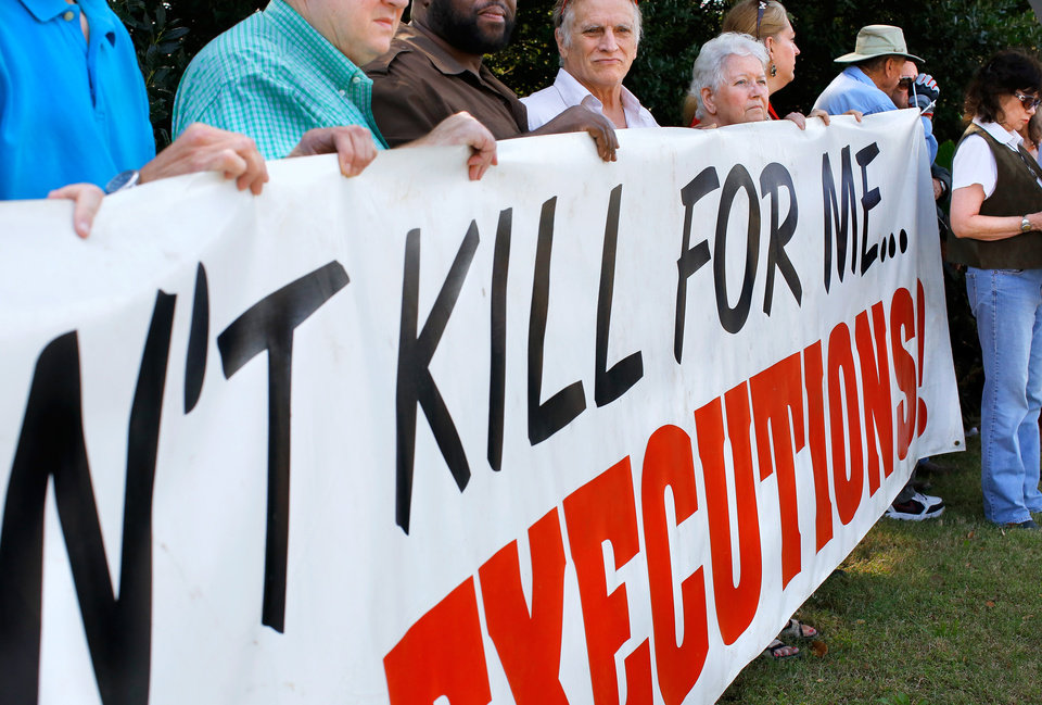 Photo - A crowd of peaceful protestors gathered along NE 23 Street in front of the Governor's Mansion in Oklahoma City on  Wednesday, Sep. 30, 2015, to keep a silent vigil as the scheduled time drew near for the execution of convicted killer Richard Glossip at the state penitentiary in McAlester. As many as 40 people held banners, waved signs and waved as honking motorists passed during their nearly two-hour long vigil.  Several groups were represented among the protestors, including the Oklahoma Coalition to Abolish the Death Penalty, The Norman community of Quakers and Amnesty International. Glossip, 52, received a last minute stay from Gov. Mary Fallin. He was scheduled to to die at 3 p.m. Wednesday after being convicted in two separate trials in the 1997 beating death of his boss, Barry Van Treese. Photo by Jim Beckel, The Oklahoman.
