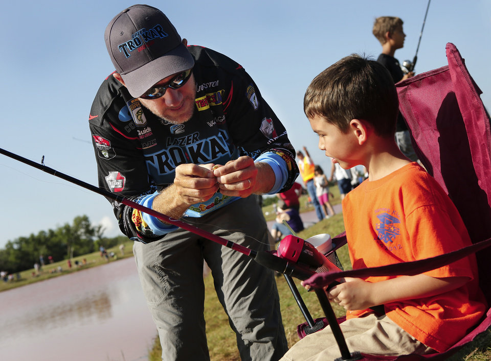 Photo - 2012 Bassmaster Angler of the Year Brent Chapman, from Lake Quivira, KS, baits a hook for 6 year-old angler Tristan Perez of Moore. Moore hosted its annual kids fishing derby Saturday morning, July 27, 2013,  at Buck Thomas Park.  As part of the event this year, a charity called the Tackle the Storm Foundation handed out rods and reels to tornado victims. Several bass fishing pros from Oklahoma attended the event to help distribute the fishing equipment and share fishing tips with the young anglers. An event official  said about 250 children participated in the fishing derby. Photo  by Jim Beckel, The Oklahoman.