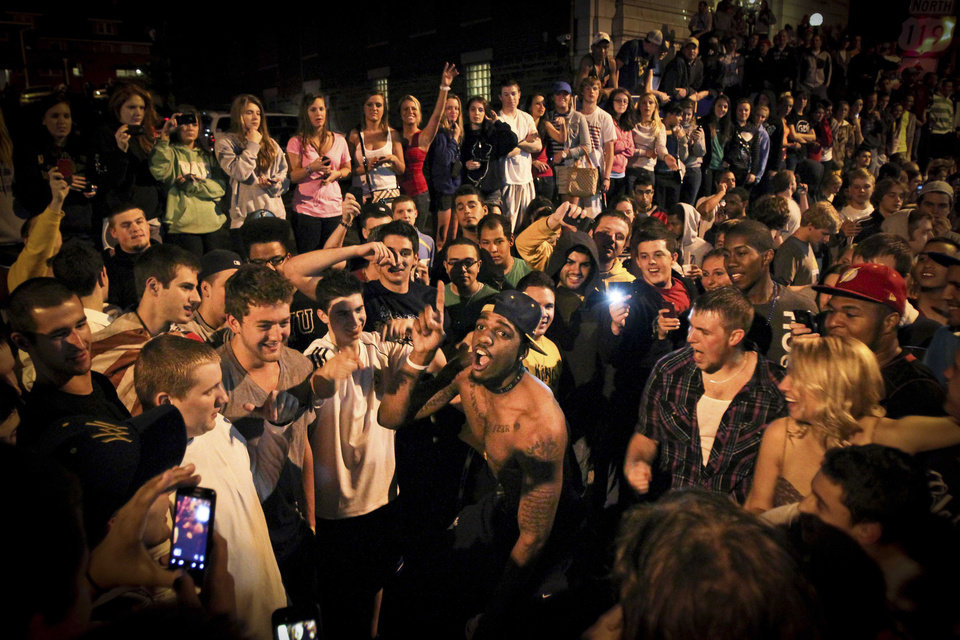 Photo - John Flowers, graduating WVU basketball forward, center, prepares to jump as hundreds of fellow students celebrate the death of Osama Bin Laden in Morgantown W.V. early Monday, May 2, 2011. Osama bin Laden, the face of global terrorism and architect of the Sept. 11, 2001, attacks, was killed in a firefight with elite American forces in Pakistan on Monday, May 2, 2011 then quickly buried at sea. (AP Photo/Daily Athenaeum, Matt Sunday) ORG XMIT: WVMOA102