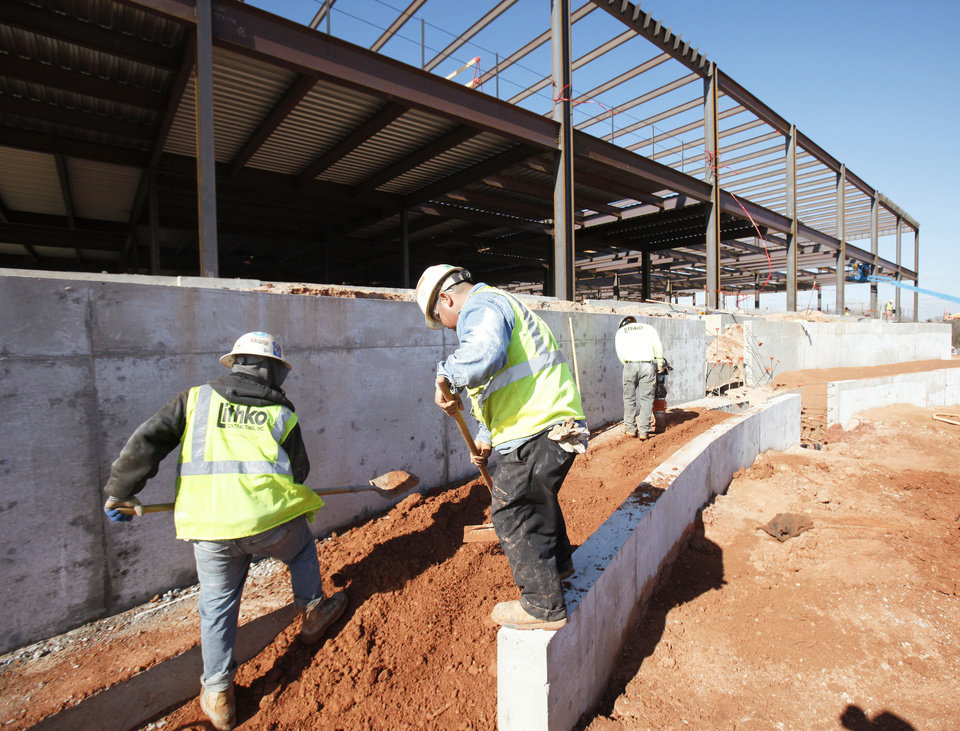 Workers pack dirt for one of the sidewalks at the new Mercy Health System complex in Edmond.  PHOTO BY PAUL HELLSTERN, THE OKLAHOMAN