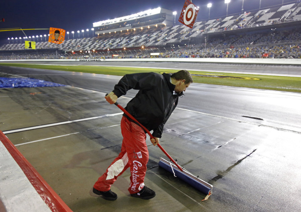 Photo - A crew member uses a squeegee to remove water from pit road during a rain delay in the NASCAR Daytona 500 Sprint Cup series auto race at Daytona International Speedway in Daytona Beach, Fla., Sunday, Feb. 23, 2014. (AP Photo/Terry Renna)
