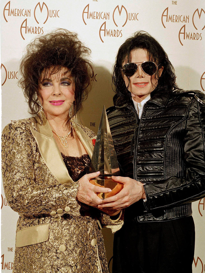 FILE - In this Jan. 25, 1993 file photo, Pop singer Michael Jackson, right, holds his award while posing with actress Elizabeth Taylor at the 20th American Music Awards held at the Shrine Auditorium in Los Angeles.  (AP Photo/Mark Terrill, file) ORG XMIT: NYET714