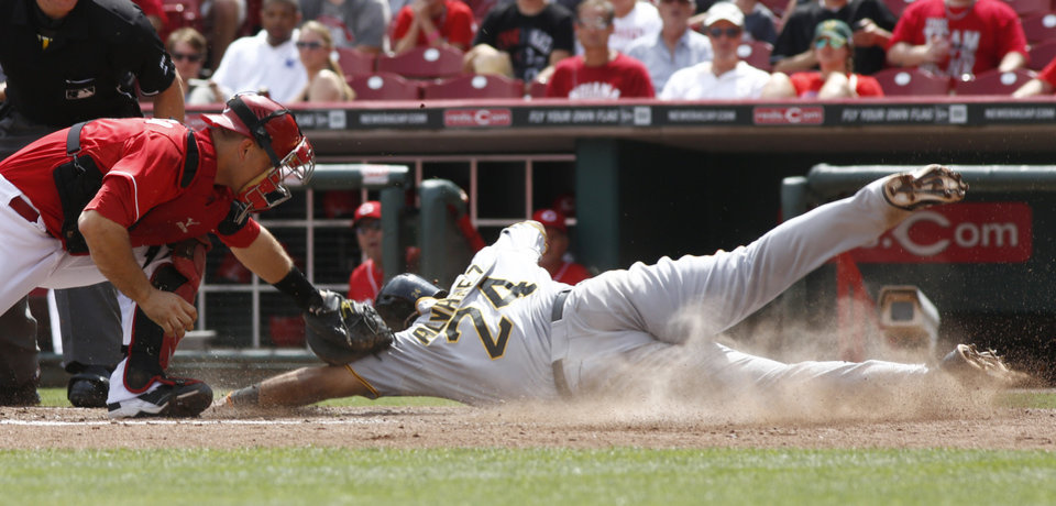 Photo - Pittsburgh Pirates' Pedro Alvarez (24) scores at home beating the tag from Cincinnati Reds catcher Devin Mesoraco, left, in the fifth inning of a baseball game, Sunday, July 13, 2014, in Cincinnati. (AP Photo/David Kohl)