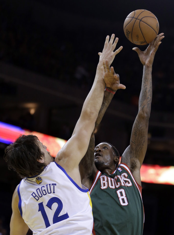Milwaukee Bucks' Larry Sanders, right, shoots over Golden State Warriors' Andrew Bogut (12) during the first half of an NBA basketball game on Saturday, March 9, 2013, in Oakland, Calif. (AP Photo/Ben Margot)