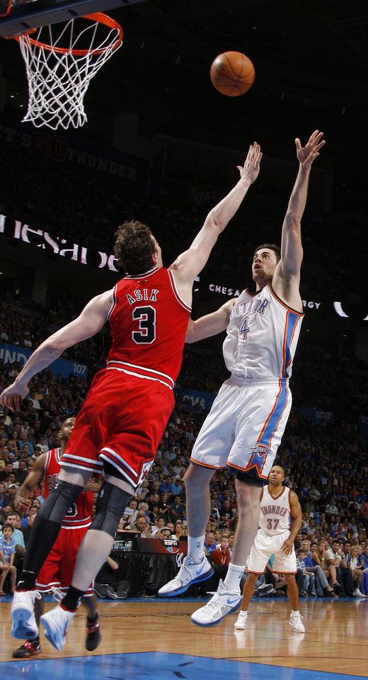 Oklahoma City's Nick Collison (4) shoots over Chicago's Omer Asik (3) during the NBA basketball game between the Chicago Bulls and the Oklahoma City Thunder at Chesapeake Energy Arena in Oklahoma City, Sunday, April 1, 2012. Photo by Sarah Phipps, The Oklahoman