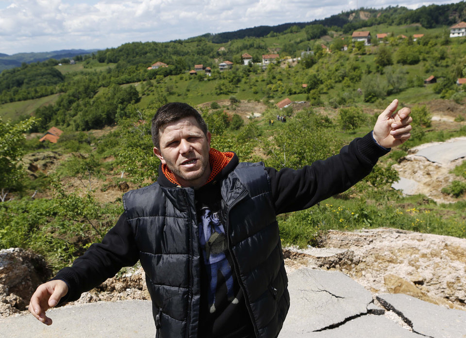 Photo - Bosnian man Mesan Ikanovic gestures as he explains how he lost his house in a landslide near Kalesija, Bosnia, 150 kms north of Sarajevo, Sunday May 18, 2014. Packed into buses, boats and helicopters, carrying nothing but a handful of belongings, tens of thousands fled their homes in Bosnia and Serbia, seeking to escape the worst flooding in a century. (AP Photo/Amel Emric)