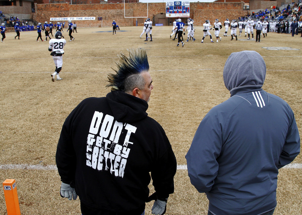 Photo - Doc Blassingame, left,  father of Guthrie High School defensive lineman Trevor Blassingame, talks to a friend while standing at the back of the end zone during Guthrie's playoffs game with Shawnee.  Doc wears his dyed blue hair in a Mohawk style to the games  after promising Trevor during his freshman year he would sport one when  he became a starter on the varsity squad. Guthrie Bluejays defeated Shawnee Wolves, 23-21, in  a high school football Class 5A round two playoff game in Guthrie on Saturday afternoon,  Nov. 23, 2013.     Photo by Jim Beckel, The Oklahoman