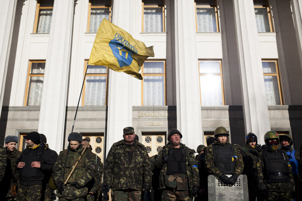 Photo - Self defense volunteers line up outside the Parliament in Kiev, Ukraine, Monday, March 17, 2014. A referendum held in Crimea on Sunday was widely condemned by Western leaders who were planning to discuss economic sanctions to punish Russia on Monday. Ukraine's new government in Kiev called the referendum a