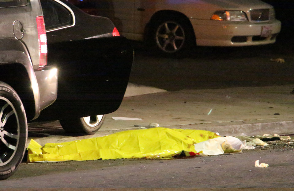 Photo - In this image provided by KEYT-TV, a body is covered on the ground after a mass shooting near the campus of the University of Santa Barbara in Isla Vista, Calif., Friday, May 23, 2014.  A drive-by shooter went on a