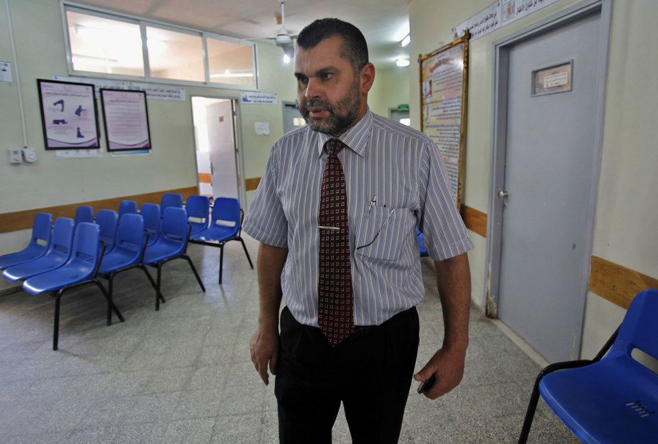 Photo - In this Tuesday, June 25, 2013 photo, Dr. Salah Rantisi walks between rooms at Khan Younis government clinic during an Interview in Khan Younis Refugee Camp, southern Gaza Strip, Thursday, June 27, 2013. On the day of his induction, Baraa Rantisi, Salah's nephew, was told to wait near a mosque. A white car drove up. Secret passwords were exchanged. And then he was sworn into the Muslim Brotherhood, an exclusive movement that sees itself on a divine mission to establish Islamic rule. AP reporters got rare access to the Rantisi family, the closest thing to a royal clan in the Brotherhood in Gaza, at a time when the movement is under siege throughout the region. (AP Photo/Adel Hana)