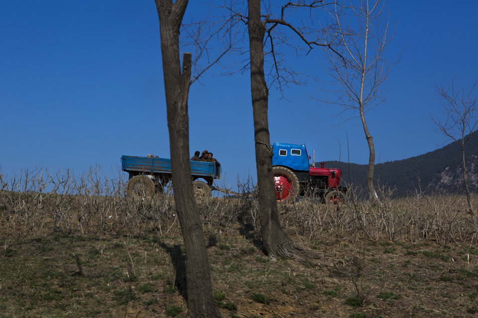 In this April 24, 2013 photo, North Koreans ride in a tractor-pull wagon in a field north of Kaesong, North Korea. (AP Photo/David Guttenfelder)