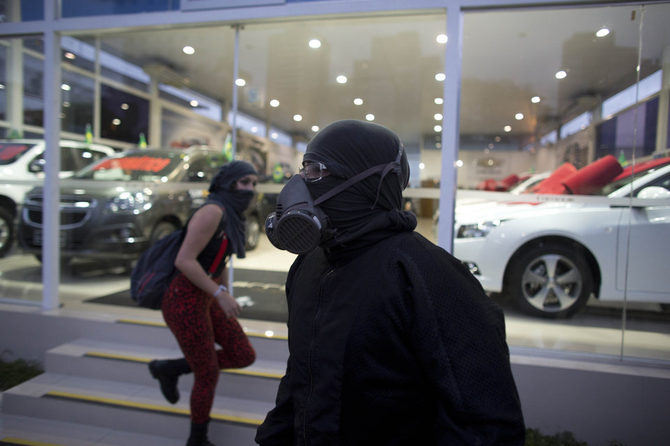 Photo - Masked protesters tried to keep others from vandalizing a car dealership while marching in Sao Paulo, Brazil, Thursday, June 19, 2014.  A protest in Brazil's biggest city that is hosting a World Cup match has drawn upward of 2,000 people. The protest in Sao Paulo was called by the Free Fare movement, the group that was behind the first protests last year that sparked roiling anti-government demonstrations across Brazil.(AP Photo/Dario Lopez-Mills)