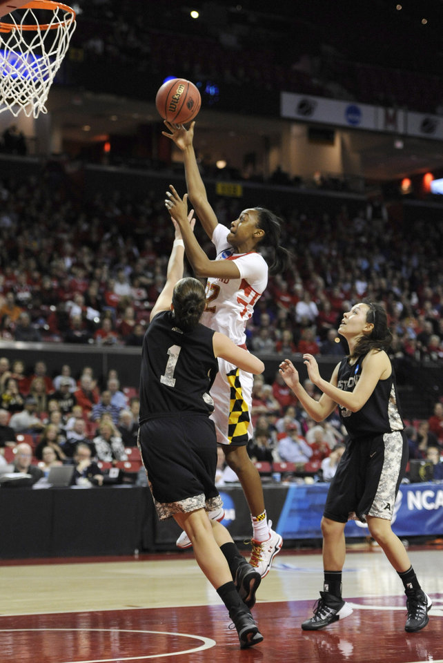 Photo - Maryland's Shatori Walker- Kimbrough, top, shoots as Army's Jen Hazlett (1) and Kelsey Minato defend during the first half of the first round of the NCAA women's college basketball tournament, Sunday, March 23, 2014, in College Park, Md.(AP Photo/Gail Burton)
