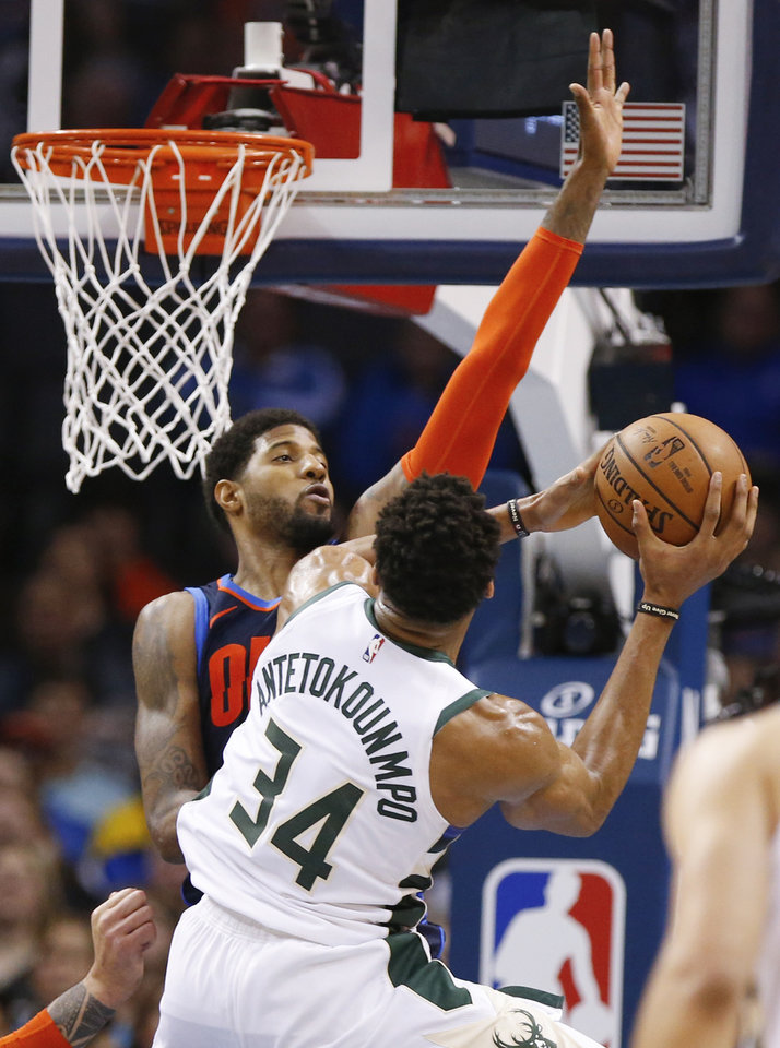 Photo - Oklahoma City's Paul George (13) defends Milwaukee's Giannis Antetokounmpo (34) in the fourth quarter during an NBA basketball game between the Milwaukee Bucks and the Oklahoma City Thunder at Chesapeake Energy Arena in Oklahoma City, Sunday, Jan. 27, 2019. Oklahoma City won 118-112. Photo by Nate Billings, The Oklahoman