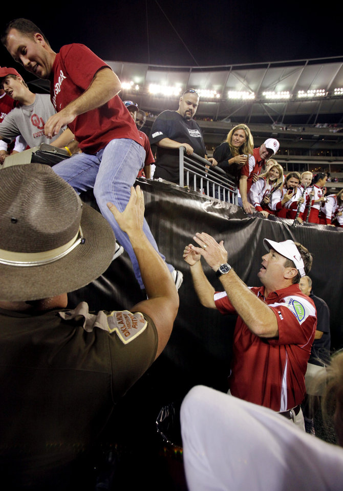 Photo - Head coach Bob Stoops helps a nephew down from the stands to join him saying