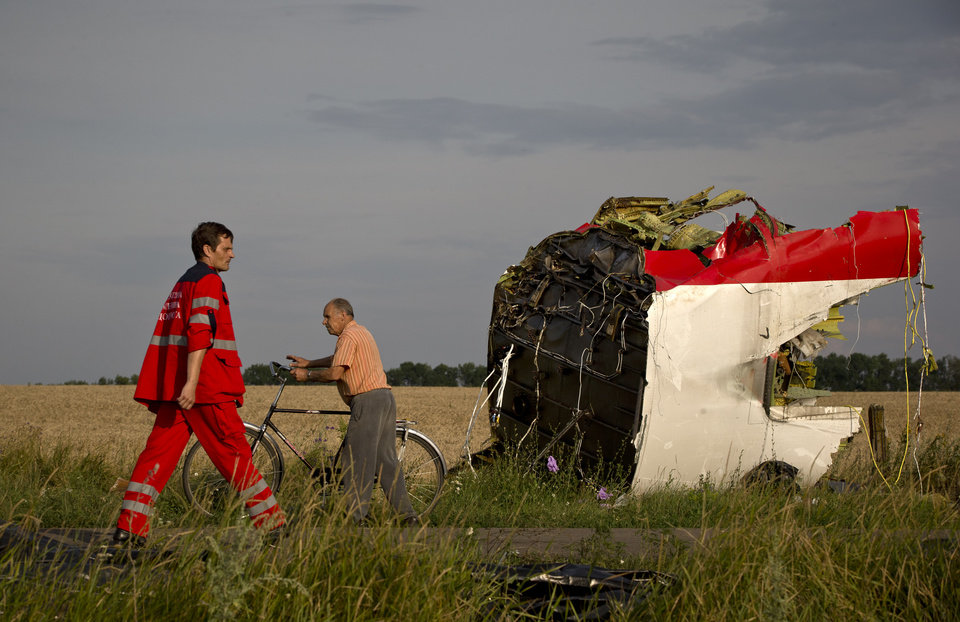 Photo - A paramedic walks by a part of fuselage at the crash site of Malaysia Airlines Flight 17 near the village of Hrabove, eastern Ukraine, Saturday, July 19, 2014. World leaders demanded Friday that pro-Russia rebels who control the eastern Ukraine crash site of Malaysia Airlines Flight 17 give immediate, unfettered access to independent investigators to determine who shot down the plane. (AP Photo/Vadim Ghirda)