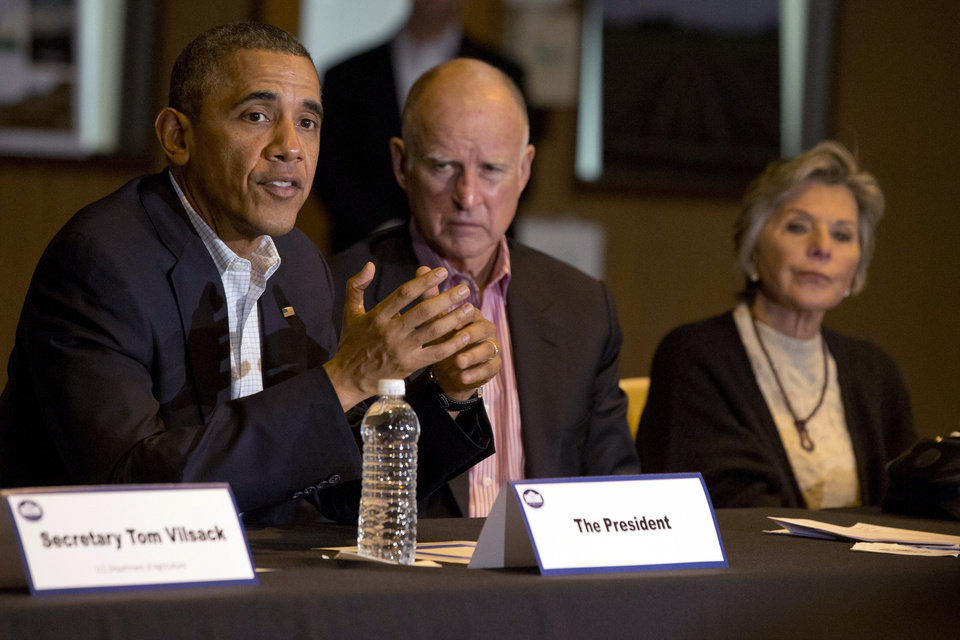 Photo - President Barack Obama, left, speaks during a roundtable with community leaders including California Gov. Jerry Brown, and Sen. Barbara Boxer, D-Calif., at San Luis Water Facility in Firebaugh, Calif., Friday, Feb. 14, 2014, regarding the ongoing drought. (AP Photo/Jacquelyn Martin)