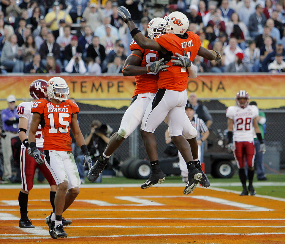 Photo - CELEBRATION: Oklahoma State's Brandon Pettigrew (87) and Dez Bryant (1) celebrate after Bryant's touchdown in the first half during the Insight Bowl college football game between Oklahoma State University (OSU) and the Indiana University Hoosiers (IU) at Sun Devil Stadium on Monday, Dec. 31, 2007, in Tempe, Ariz.   BY NATE BILLINGS, THE OKLAHOMAN ORG XMIT: KOD