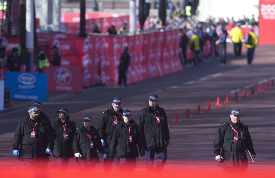 Photo - British police officers make final checks in the Mall, prior to the beginning of the London Marathon near to the finish line for marathon is situated in London, Sunday, April  21, 2013. Security has been stepped up in London following the recent bombs at the Boston Marathon. The London Marathon started as planned on a glorious sunny morning Sunday despite concerns raised by the bomb attacks on the Boston Marathon six days ago. (AP Photo/Alastair Grant)