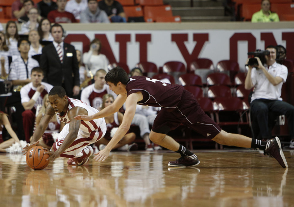 Photo - Oklahoma's Je'Lon Hornbeak (5) and Louisiana's Trent Mackey (5) dive for a ball during a men's college basketball game between the University of Oklahoma and the University of Louisiana-Monroe at the Loyd Noble Center in Norman, Okla., Sunday, Nov. 11, 2012.  Photo by Garett Fisbeck, The Oklahoman
