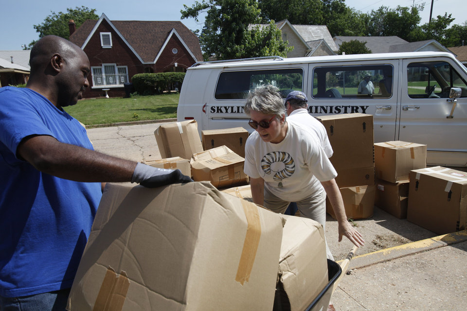 Photo - John Myers, a deacon with Wheeler Avenue Baptist Church in Houston, Texas, helps Martha Tehan of Edmond load boxes of donations into a wheelbarrow to take into Christ United Methodist Church in Oklahoma City.    Aliki Dyer - The Oklahoman