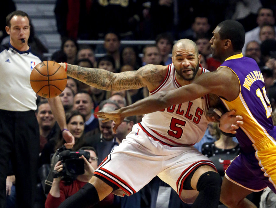 Los Angeles Lakers forward Metta World Peace (15) challenges Chicago Bulls forward Carlos Boozer (5) during the first half of an NBA basketball game, Monday, Jan. 21, 2013, in Chicago. (AP Photo/Charles Rex Arbogast)