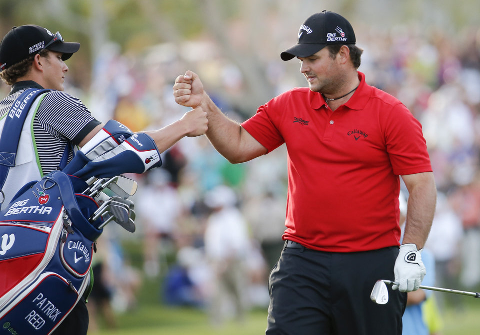 Photo - Patrick Reed, right, celebrates with his caddie Kessler Karain after winning the Humana Challenge golf tournament on the Palmer Private course at PGA West, Sunday, Jan. 19, 2014 in La Quinta, Calif. (AP Photo/Matt York)