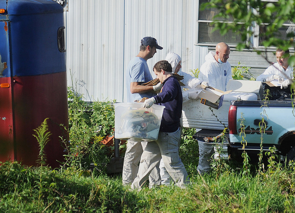 Photo - New York State Police crime scene investigators carry items from the bed of a pickup truck at the home of Stephen Howells II and Nicole F. Vaisey, in Hermon, N.Y., Sunday, Aug. 17, 2014. Vaisey and Howells were arrested Friday on charges of first-degree kidnapping with the intent to physically harm or sexually abuse two Amish sister. (AP Photo/Watertown Daily Times, Melanie Kimber Lago)