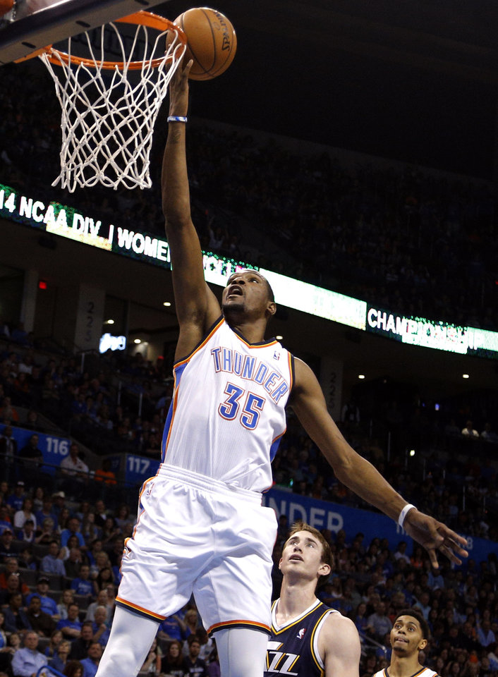 Photo - Oklahoma City 's Kevin Durant (35) shoots a lay up in front of Utah's Gordon Hayward (20) during the NBA game between the Oklahoma City Thunder and the Utah Jazz at the Chesapeake Energy Arena, Sunday, March 30, 2014, in Oklahoma City. Photo by Sarah Phipps, The Oklahoman
