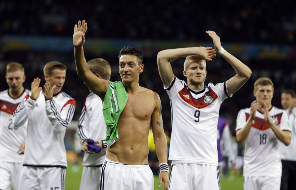 Photo - Germany's Mesut Ozil, left, and teammate Andre Schuerrle (9) celebrate after Germany defeated Algeria 2-1 in extra time during the World Cup round of 16 soccer match between Germany and Algeria at the Estadio Beira-Rio in Porto Alegre, Brazil, Monday, June 30, 2014. (AP Photo/Kirsty Wigglesworth)