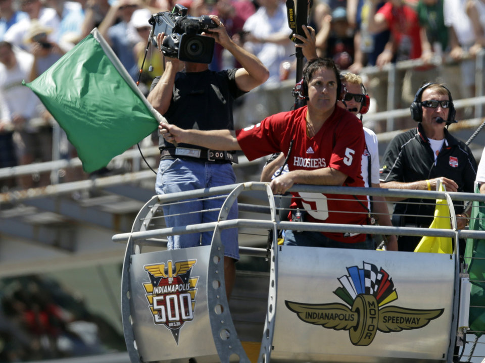 Photo - Dallas Mavericks owner Mark Cuban waves the green flag to start the 98th running of the Indianapolis 500 IndyCar auto race at the Indianapolis Motor Speedway in Indianapolis, Sunday, May 25, 2014. (AP Photo/Michael Conroy)