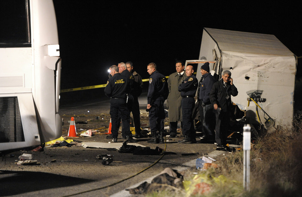 Photo - Authorities continue their investigation of the scene where at least eight people were killed and 38 people were injured after a tour bus, left, carrying a group from Tijuana, Mexico crashed with two other vehicles just north of Yucaipa, Calif., Sunday, Feb. 3, 2013. (AP Photos/Rodrigo Pena)
