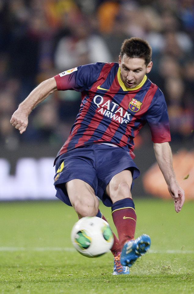 Photo - FILE - The Jan. 8, 2014 file photo shows FC Barcelona's Lionel Messi, from Argentina,  kicking the ball to score against Getafe during a Copa del Rey soccer match at the Camp Nou stadium in Barcelona, Spain. Messi is one of the three candidates as the world's best soccer player  to be awarded at the FIFA Ballon d'Or gala on Monday, Jan 13, 2014.  (AP Photo/Manu Fernandez, file)