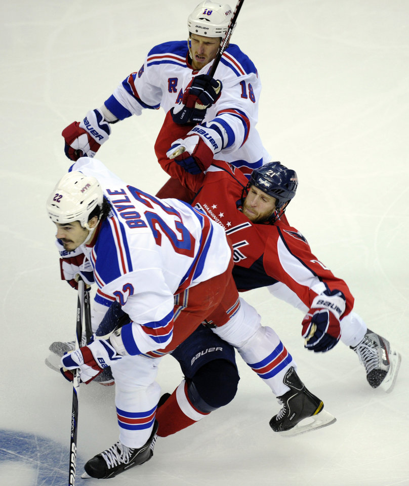 Photo -   Washington Capitals center Brooks Laich (21) gets caught between New York Rangers defenseman Ryan McDonagh (27) and defenseman Marc Staal (18) during the first period of Game 3 of their NHL hockey Stanley Cup second-round playoff series at the Verizon Center in Washington, Wednesday, May 2, 2012. (AP Photo/Susan Walsh)