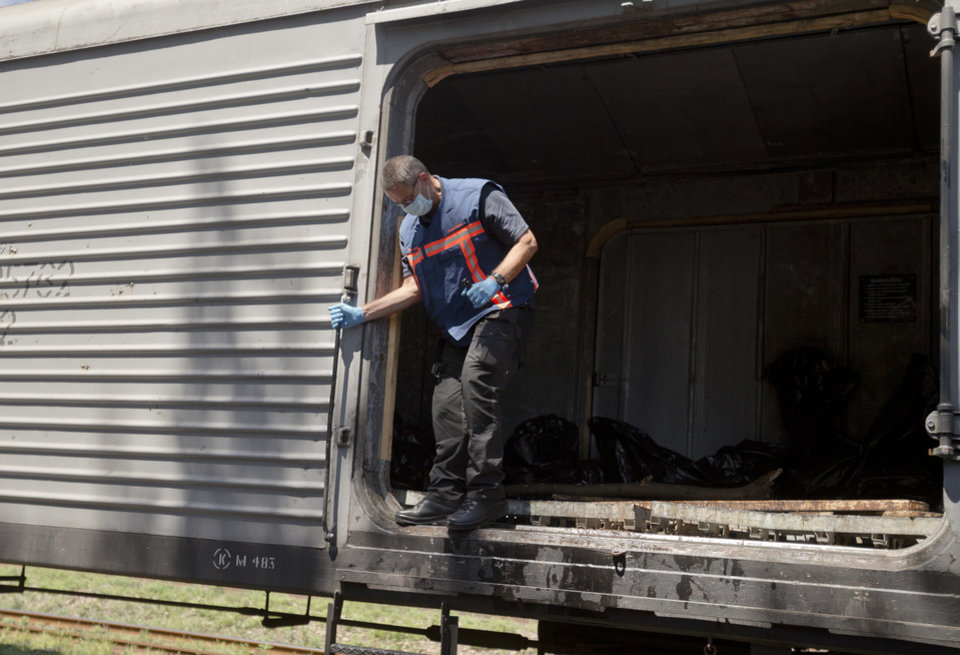 Photo - Peter Van Vilet, team leader of Netherlands' National Forensic Investigations Team exits a carriage while inspecting a refrigerated train loaded with the bodies of passengers moved from the crash site of Malaysia Airlines Flight 17, located 15 kilometers (9 miles) away, in Torez, eastern Ukraine, Monday, July 21, 2014. Another 21 bodies have been found in the sprawling fields of east Ukraine where Malaysia Airlines Flight 17 was downed last week, killing all 298 people aboard. (AP Photo/Vadim Ghirda)