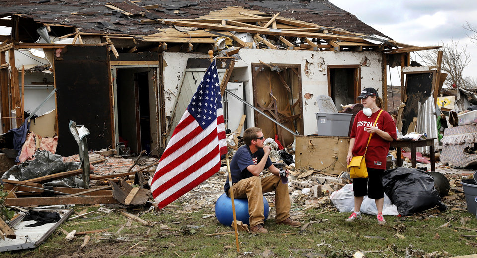 Photo - Dan Wiechmann came down from his job in Minnesota to help the Moore tornado victims. He sits in the front yard of a heavily damaged home talking to another volunteer and drinking liquids during a short break in clean-up efforts Saturday. The volunteers said the American flag was already planted in the yard when they arrived at the house. Volunteers from various parts of the country joined Oklahomans in assisting residents on Saturday,  May 25, 2013, doing whatever was needed to remove debris and salvage items from this neighborhood east of Santa Fe, north of SW 19 Street.  An EF5 tornado leveled many neighborhoods in Moore and southwest Oklahoma City last Monday.   Photo  by Jim Beckel, The Oklahoman.