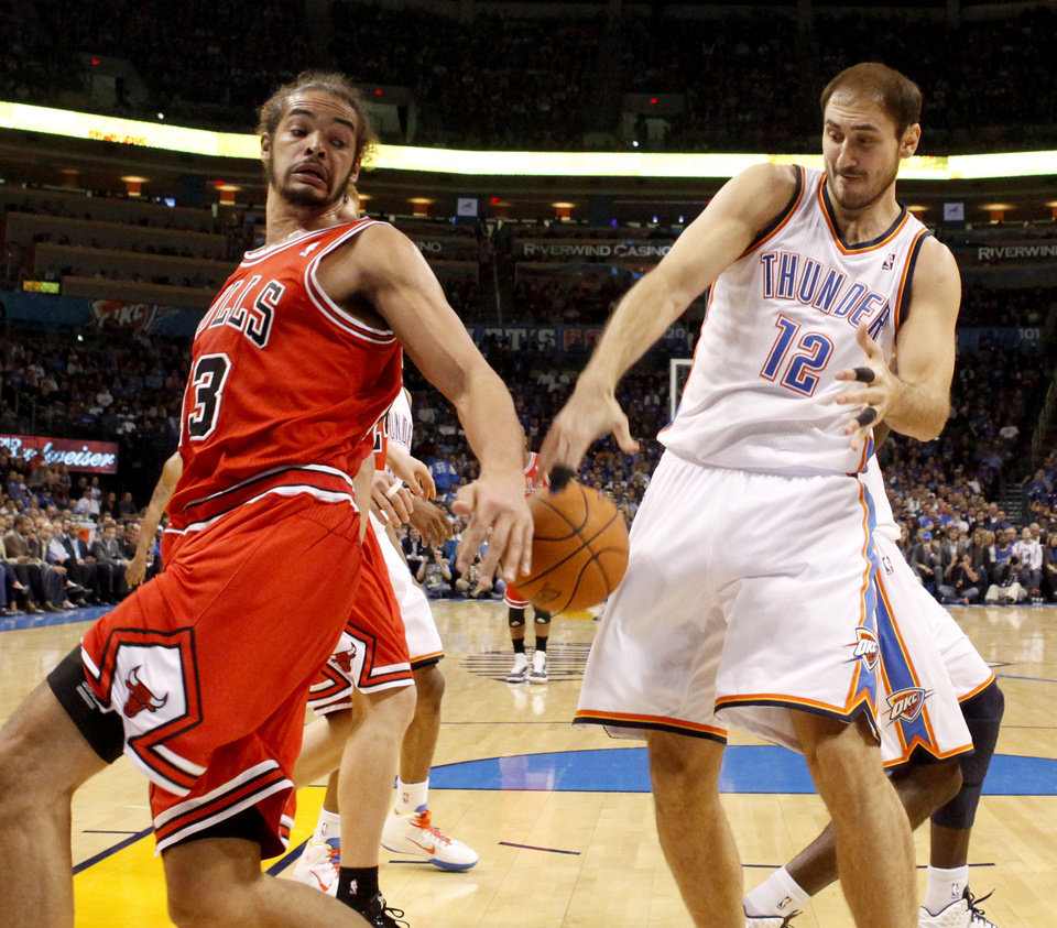 Photo - Oklahoma City's Nenad Krstic and Chicago's Joakim Noah fight for the ball during the NBA basketball game between the Oklahoma City Thunder and the Chicago Bulls in the Oklahoma City Arena on Wednesday, Oct. 27, 2010. Photo by Bryan Terry, The Oklahoman
