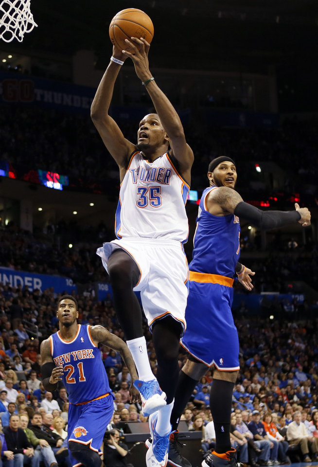 Oklahoma City\'s Kevin Durant (35) takes the ball to the hoop past New York\'s Carmelo Anthony (7) and Iman Shumpert (21) during an NBA basketball game between the New York Knicks and the Oklahoma City Thunder at Chesapeake Energy Arena in Oklahoma City, Sunday, Feb. 9, 2014. Photo by Nate Billings, The Oklahoman