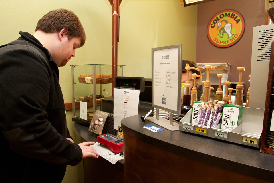 Photo - Christopher Jacques, 22, uses his index finger to pay for an Italian soda at a coffee shop at the South Dakota School of Mines and Technology on Friday Feb. 15, 2013. Jacques, an electrical engineering major from Pacific, Wash., is one of about 50 students and four faculty members at the school enrolled in a pilot program that uses Biocryptology -- or one's fingerprint and hemoglobin -- in place of cash or credit cards to pay for items. (AP Photo, Amber Hunt)